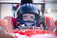 Portrait confident male formula one race car driver gesturing thumbs-up - CAIF06496