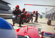 Pit crew with tires ready for nearing formula one race car in pit lane - CAIF06499