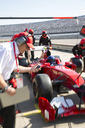 Manager with stopwatch timing pit crew replacing tires on formula one race car in practice session pit lane - CAIF06502