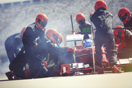 Pit crew replacing tires on formula one race car in pit lane - CAIF06511