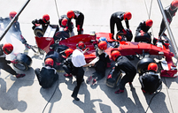 Manager with stopwatch timing pit crew replacing tires on formula one race car in pit lane - CAIF06520