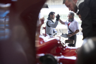 Manager and formula one race car driver high-fiving in repair garage - CAIF06529