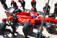 Pit crew replacing tires on formula one race car in pit lane - CAIF06532