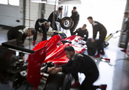 Pit crew working on formula one race car in repair garage - CAIF06535