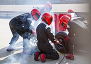 Pit crew replacing tires on formula one race car in pit lane - CAIF06538