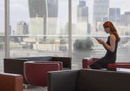 Businesswoman texting with cell phone in urban lounge with city view - CAIF06547