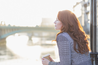 Serene businesswoman with red hair drinking coffee at urban waterfront - CAIF06556
