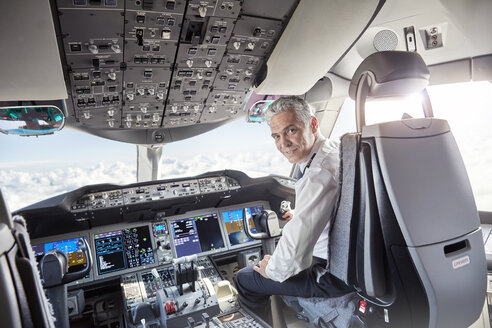 Portrait confident male pilot in airplane cockpit - CAIF06565