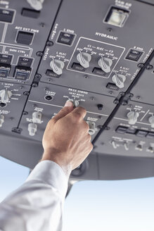 Pilot adjusting control instruments in airplane cockpit - CAIF06568