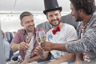Young male friends toasting champagne glasses on airplane - CAIF06571