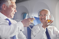 Businessman toasting whiskey glasses in first class on airplane - CAIF06577