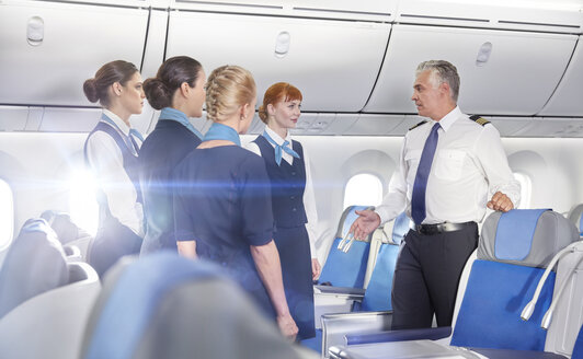 Pilot and flight attendants talking, preparing on airplane - CAIF06580