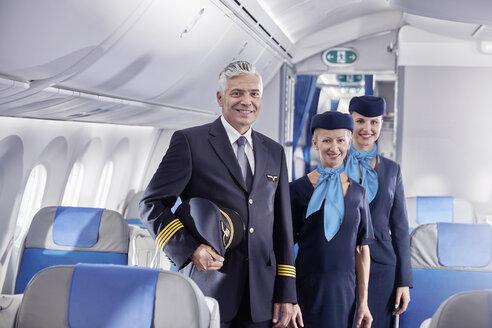 Portrait confident pilot and flight attendants on airplane - CAIF06589