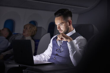 Serious businessman working at laptop on overnight airplane - CAIF06592