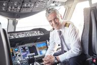 Portrait confident male pilot in airplane cockpit - CAIF06598