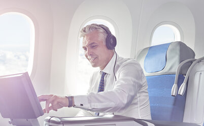 Businessman with headphones watching movie on airplane - CAIF06601