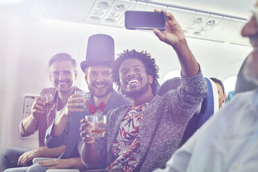 Enthusiastic young male friends with camera phone drinking and taking selfie on airplane - CAIF06604