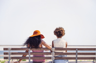 Female friends sitting on bench by sea - CAVF01097