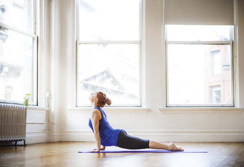 Pregnant woman practicing upward facing dog position in gym - CAVF01136