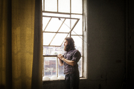 Thoughtful man standing by window at home - CAVF01151