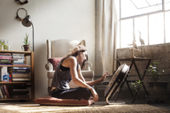 Side view of woman sitting in front of electric fan at home - CAVF01154