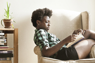 Woman reading book while sitting on armchair at home - CAVF01160