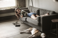 Woman looking at dog while lying on sofa at home - CAVF01172