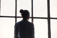 Rear view of woman standing by window at home - CAVF01184