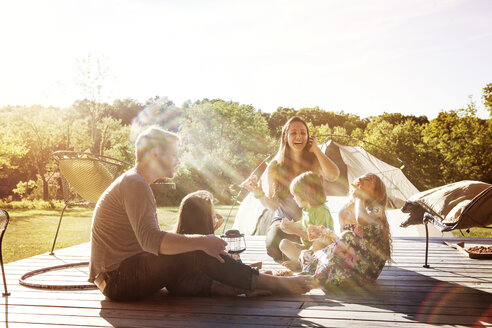 Happy family sitting on porch - CAVF01205