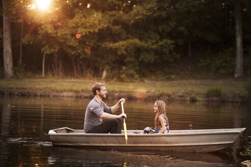 Father with daughter oaring boat in lake - CAVF01214