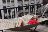 Woman relaxing on hammock in patio - CAVF01253