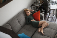 High angle view of woman relaxing on sofa at home - CAVF01256