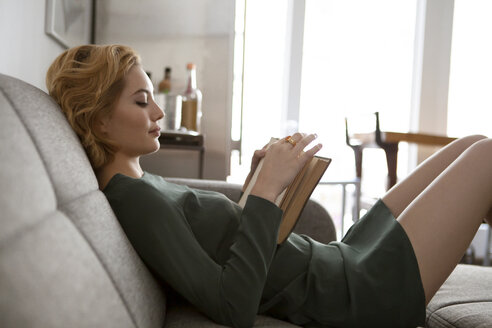 Side view of woman reading book while reclining on sofa at home - CAVF01259