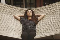 Thoughtful woman lying on hammock in patio - CAVF01268