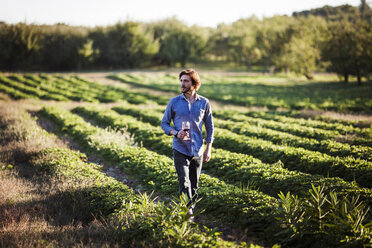 Man holding drink while walking on field at farm - CAVF01295