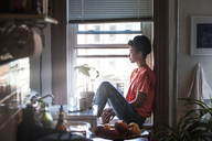 Woman looking away while sitting on window sill at home - CAVF01307
