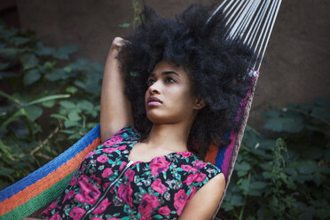 Woman with frizzy hair looking away while lying on hammock - CAVF01313