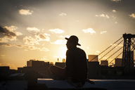Silhouette man sitting on retaining wall at terrace - CAVF01316
