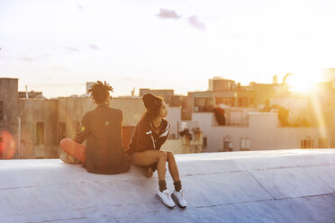 Couple sitting on retaining wall against buildings - CAVF01319