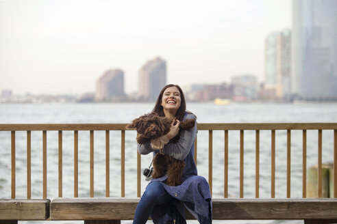 Playful woman with dog sitting on bench against Hudson River - CAVF01346