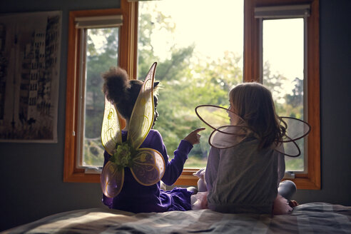 Rear view of girls in fairy costumes sitting on bed at home - CAVF01361