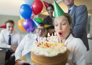 Colleagues watching businesswoman blowing out birthday cake candles - CAIF06607