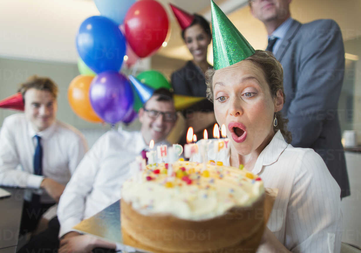 Colleagues watching businesswoman blowing out birthday cake candles - CAIF06607 - Paul Bradbury/Westend61