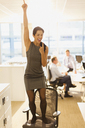 Exuberant businesswoman celebrating on top of office chair - CAIF06610