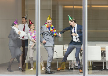 Playful business people in party hats dancing at conference room window - CAIF06616