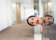 Reflection portrait of exuberant woman peering into office corridor - CAIF06622