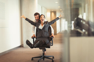 Playful businessman pushing exuberant businesswoman down corridor in office chair - CAIF06625