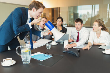 Shocked colleagues watching businessman with megaphone yelling into conference phone - CAIF06628