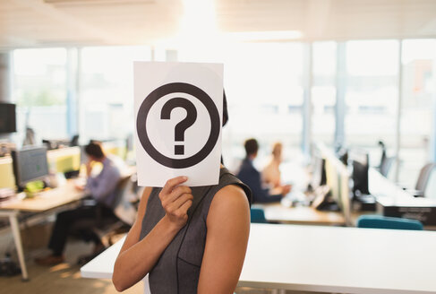 Portrait of businesswoman holding question mark printout over her face in office - CAIF06631