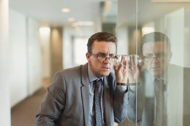 Focused businessman eavesdropping with glass in office corridor - CAIF06637
